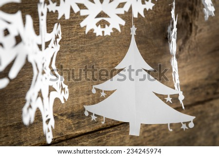 Christmas decorations snowflake ,christmas tree paper hanging over wooden background - stock photo