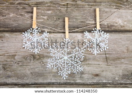 Christmas decorations, snowflakes hanging over wooden background