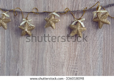 Christmas decorations (stars) hanging over wooden background