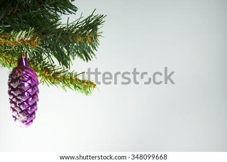 Christmas decorations violet glass pine cone spruce on Christmas tree background - stock photo