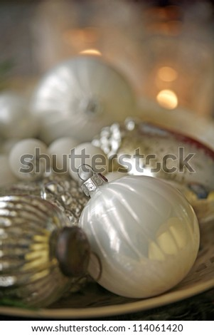 Christmas decorations: white baubles on a plate, closeup - stock photo