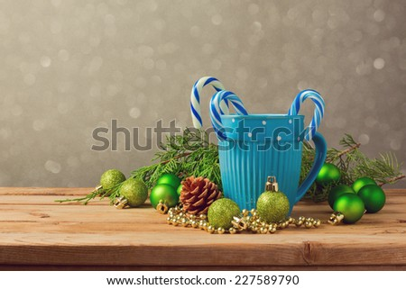 Christmas decorations with blue cup and candy on wooden table with copy space - stock photo