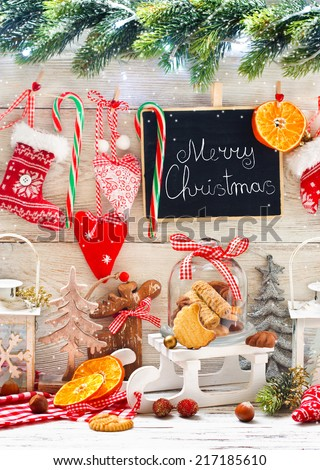 Christmas decorations with cookies in a glass bell jar on a sledge with greeting on chalk blackboard. - stock photo