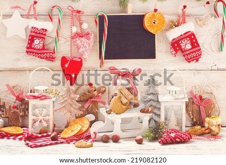 Christmas decorations with cookies in a glass bell jar on a sledge with place for greeting on chalk blackboard. Toned photo. - stock photo