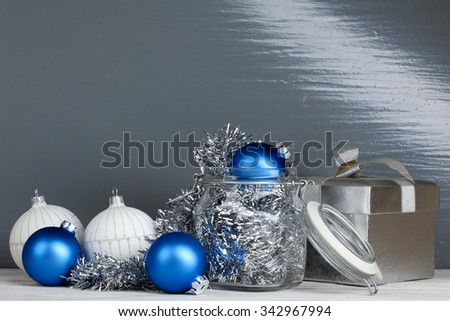 Christmas decorations with gift and Christmas balls on wooden table on grey background