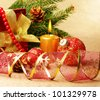 Christmas decorations with gift box over golden background - stock photo