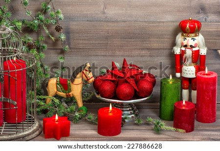 christmas decorations with red candles, baubles, antique toys nutcracker and rocking horse. retro style toned picture - stock photo