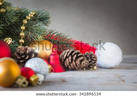 Christmas decorations with Santa Claus hat, fir and pine cones on wooden table over grunge background, selective focus - stock photo