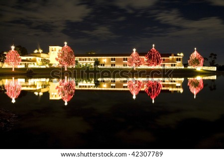 Christmas decorations with strands of  lights reflected in a lake at night. - stock photo