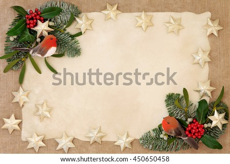 Christmas decorative background border with gold star and robin decorations, holly, ivy, mistletoe, snow covered  fir over old parchment and hemp paper. - stock photo