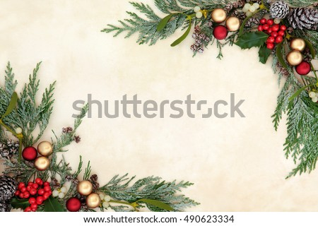 Christmas decorative background border with red and gold bauble decorations, holly, mistletoe and snow covered cedar cypress on old parchment paper.