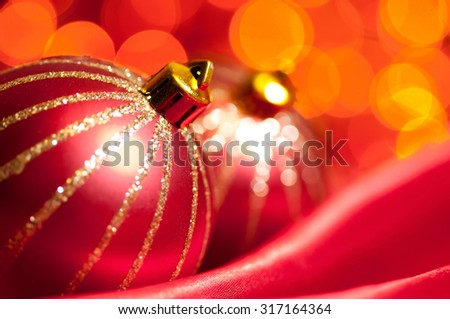 christmas decorative balls on red silk against blurred lights on background, shallow DoF - stock photo
