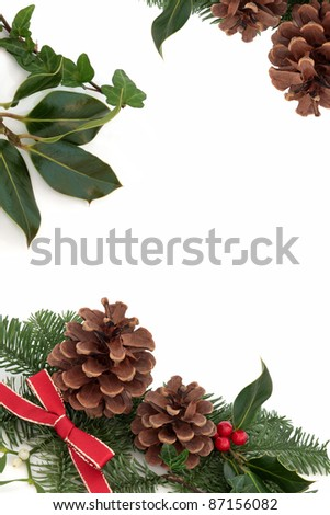 Christmas decorative border of holly, ivy, mistletoe, pine cones and blue spruce fir leaf sprig with red ribbon isolated over white background. - stock photo
