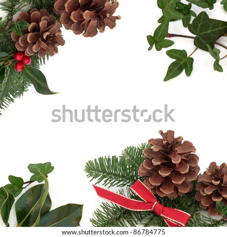 Christmas decorative border of holly, ivy, mistletoe, pine cones and spruce fir leaf sprig with red ribbon isolated over white background. - stock photo
