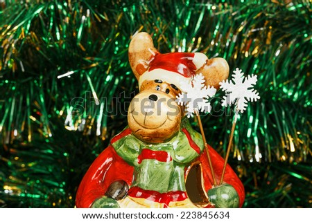 Christmas decorative deer on a green garland background - stock photo