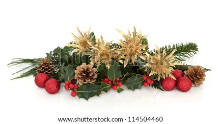 Christmas decorative flora arrangement of golden thistle, red bauble clusters, holly, ivy, spruce and cedar leaf sprigs with pine cones over white background. - stock photo