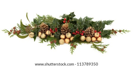 Christmas decorative floral arrangement of holly, mistletoe, ivy, cedar leaf sprigs, golden bauble clusters and pine cones over white background. - stock photo