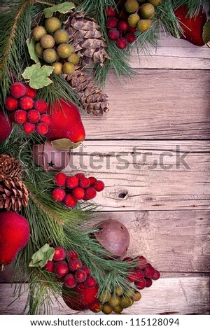 Christmas decorative fruit and pine branches on wooden background - stock photo