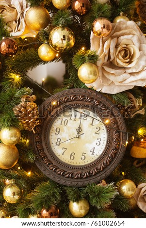 christmas decorative o'clock 12 hours gifts toys stars garland and fire in background bokeh lights holiday concept