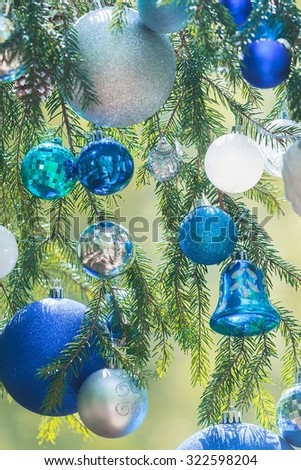 Christmas decorative shades of blue textured baubles hanging on natural spruce twigs - stock photo