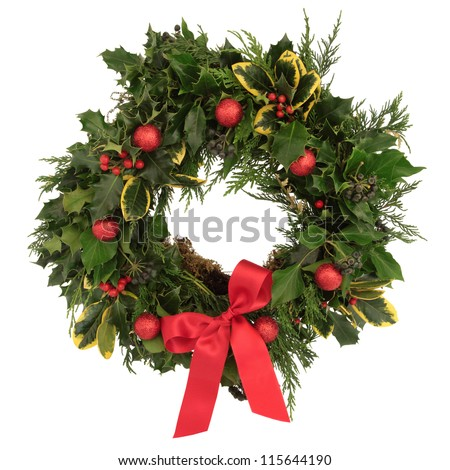 Christmas decorative wreath of holly, ivy, cedar cypress leaf sprigs and red bauble decorations with bow over white background. - stock photo