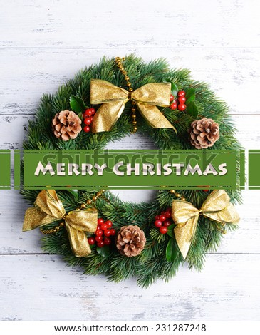Christmas decorative wreath with leafs of mistletoe on wooden background - stock photo
