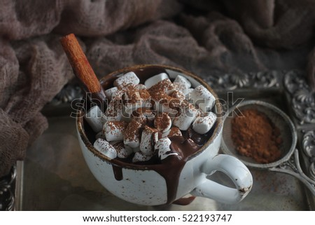Christmas delicious hot chocolate with marshmallows, nuts and cinnamon on a silver tray and vintage cloth, selective focus