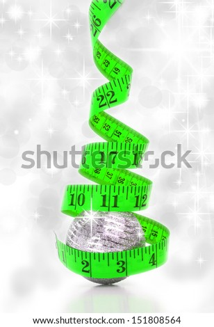 Christmas diet concept represented by a Christmas tree made from a measure tape - stock photo