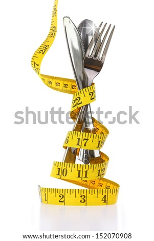 Christmas diet concept represented by a cutlery set with measuring tape - stock photo