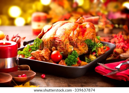 Christmas Dinner. Roasted Turkey on holiday served table, decorated with candles. Roasted chicken, table setting. - stock photo