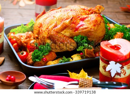 Christmas Dinner. Roasted Turkey on holiday served table. Thanksgiving table served with turkey, decorated with bright autumn leaves and candles. Roasted chicken, table setting. - stock photo
