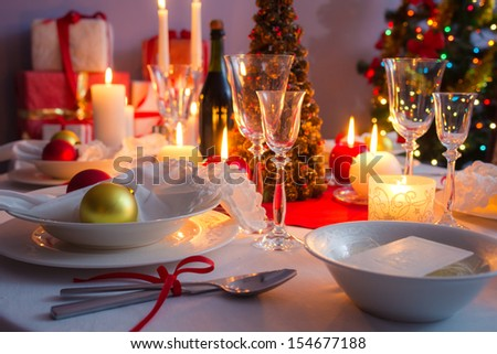 Christmas dishware on the white and red table - stock photo