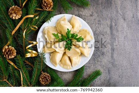 Christmas dumplings with decoration on a white plate. Top view.