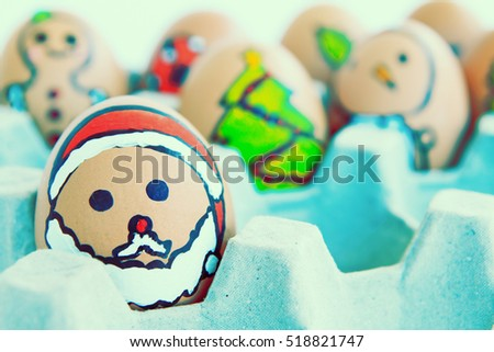 Christmas egg with faces drawn arranged in carton