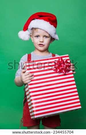 Christmas Elf holding big red gift box with ribbon. Santa Claus helper. Studio portrait over green background - stock photo