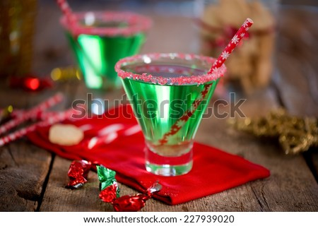 Christmas emerald green cocktail, glass rimmed with crushed candy cane. Great drink for entertaining. - stock photo