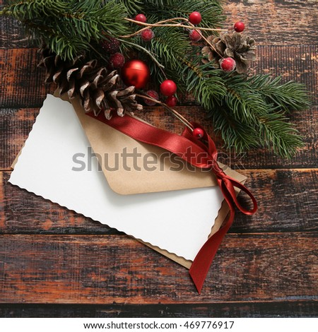 Christmas envelope with decorations over wooden background