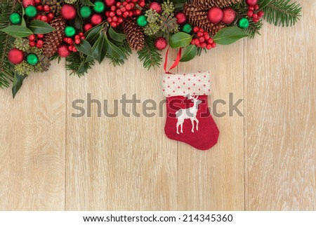 Christmas eve abstract border with stocking decoration, holly, red baubles, mistletoe and winter greenery over light oak background. - stock photo