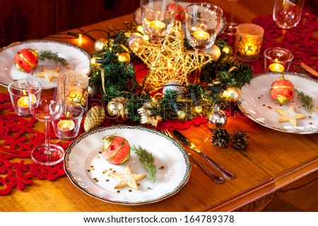 Christmas eve dinner party table setting with lights, gold glittering decorations and elegant white plates - stock photo