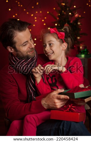 Christmas eve - happy family time. Smiling father and daughter open gifts on dark red background with lights. - stock photo