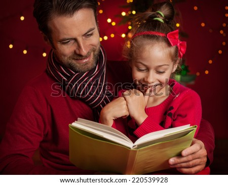 Christmas eve - happy family time. Smiling father and daughter read book on dark red background with lights. - stock photo