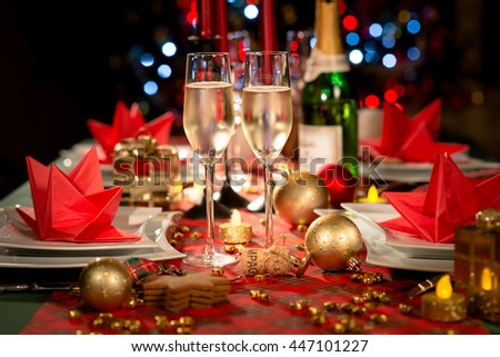 christmas eve party table with champagne flute with red and golden glitter