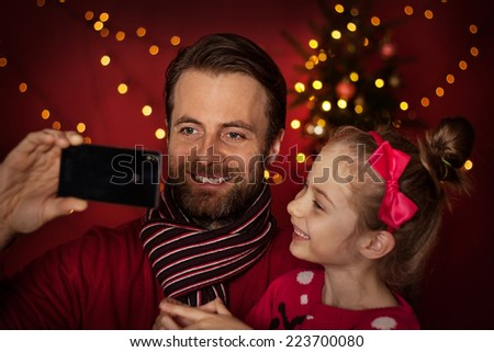 Christmas eve - smiling father and daughter taking photo of themselves (selfie) on mobile phone. Happy family time, christmas tree with lights on dark red as background. - stock photo