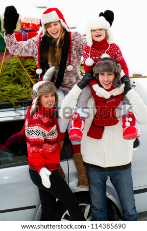 Christmas, family, celebrating - family with Christmas tree and gifts on the roof of the car - stock photo