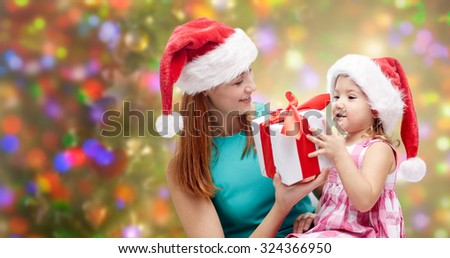 christmas, family, childhood and people concept - happy mother and little girl in santa hats with gift box over holidays lights background - stock photo