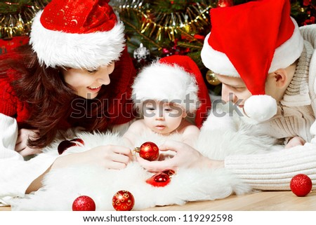 Christmas family of four persons in red hats giving gifts - stock photo