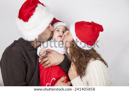 Christmas family of three persons in red hats. Happy parents and small funny baby - stock photo