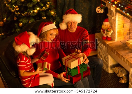 Christmas family of three persons in red hats with gift boxes - stock photo