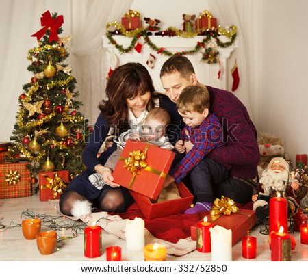Christmas Family Open Present Gift Box, Mother Father and Baby Child in Decorated Room, sitting under Christmas Tree - stock photo