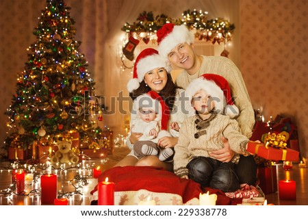 Christmas Family Portrait In Home Holiday Living Room, Kids and Baby at Santa Hat With Present Gift Box, House Decorating By Xmas Tree Candles Garland - stock photo